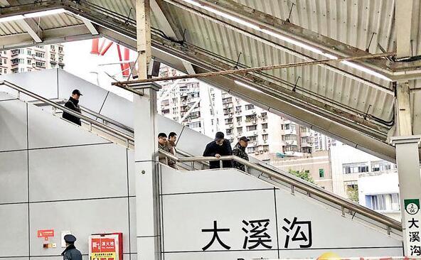 图:王家卫(右二)低调现身重庆大溪沟地铁站。
