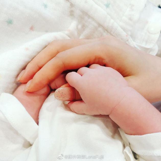 藤井莉娜牵着孩子的手
