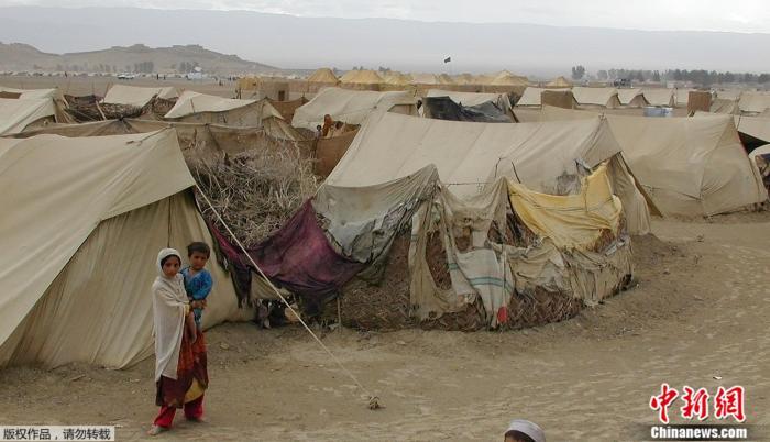 资料图:图为2012年2月15日,两名阿富汗儿童站在难民营前。