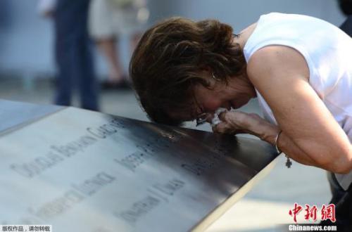 """资料图:美国纽约,民众在""""9·11""""纪念广场悼念死难者。"""