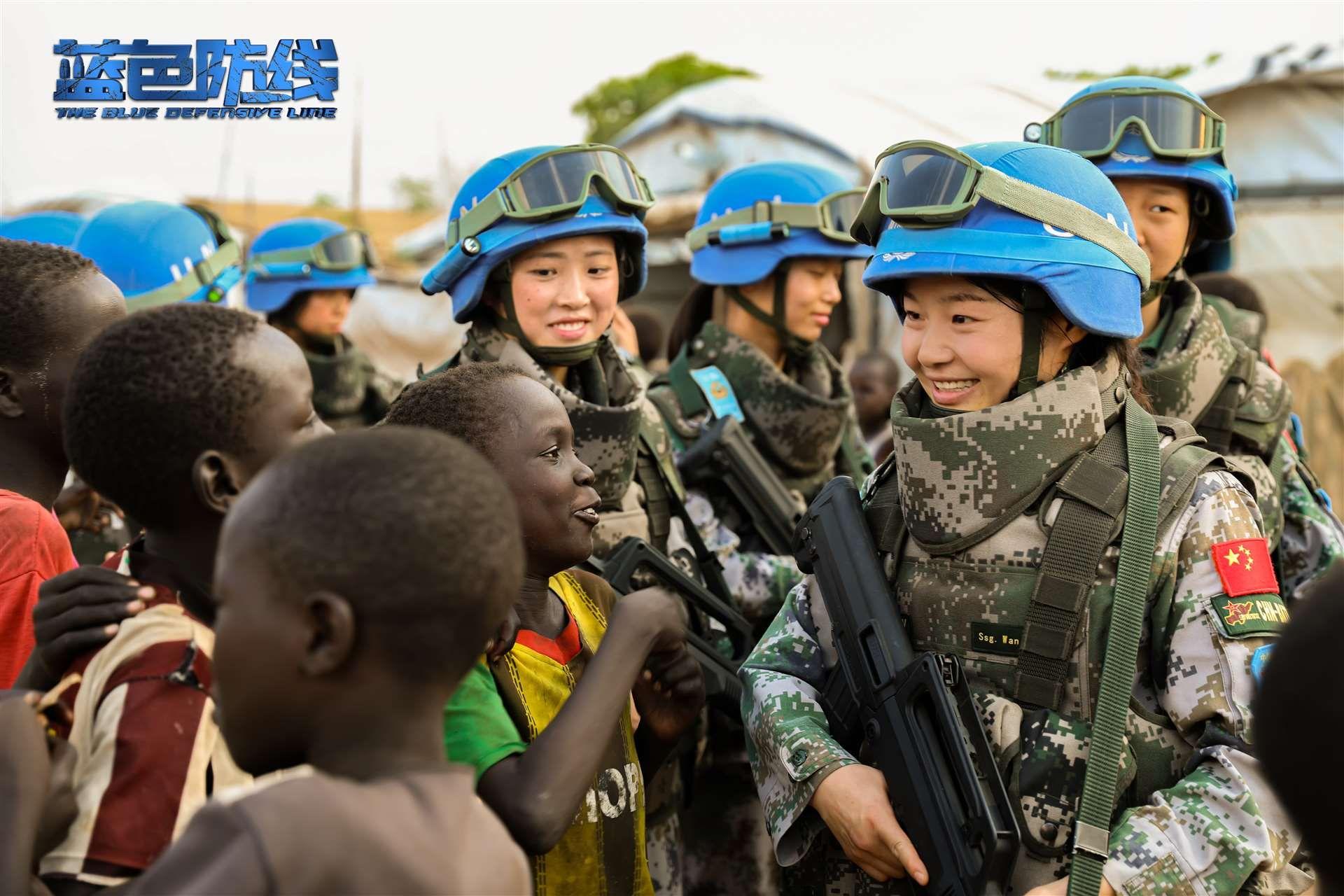 《蓝色防线》剧照,中国维和步兵营女兵与南苏丹小朋友亲切交流。